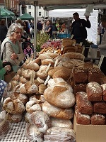 woman purchasing bread that is fresh at a farmers market